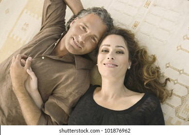 Over head portrait of a mature man and woman laying down on carpet, holding hands and smiling at camera.