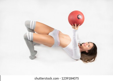 Over Head view of beautiful brunette fitness model wearing tight, short gray fitness and a white long sleeve sports top does back bridge holding a red ball over head in studio on a light background