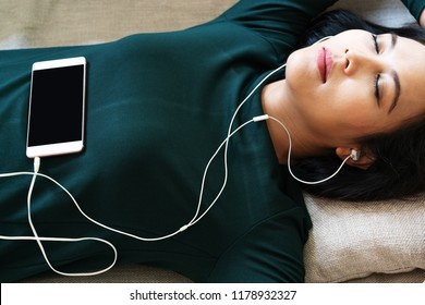 Over head view of beautiful young woman laying down on sofa using smartphone to listen the music
