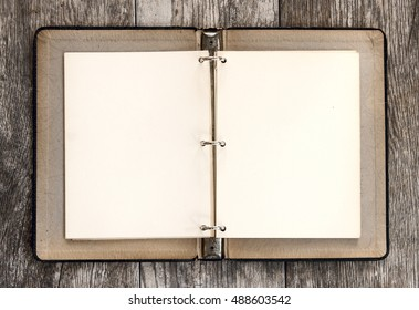 Over head view of blank open pages inside vintage three ring binder against wood grain background.