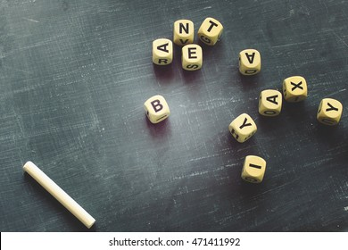 Over head view of chalkboard and chalk with alphabet letters and room for text
