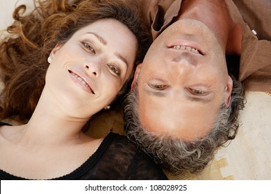Over head view of a mature couple laying down on carpet at home, smiling.