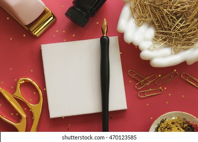Over head view of pink desk top with gold office supplies and pen and ink with room for copy. Soft glow lens background