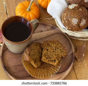 Over head view of a pumpkin muffin and cup of coffee on a wooden plate