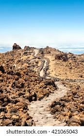 Over the Horizon. Walking road on peak of volcano mountain on a blue cloudscape background. Canary Islands, Tenerife, Spain. Multicolored outdoors vertical image.