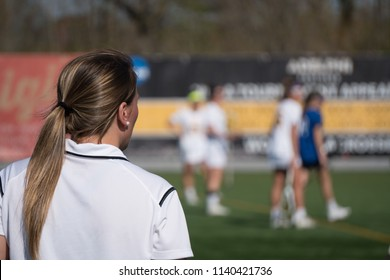 Over the shoulder female head coach on sidelines yelling play call to girl soccer players on field competing tournament match game on bright summer day in outside stadium