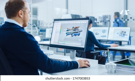 Over Shoulder: Heavy Industry Engineer Working on Personal Computer, Screen Shows CAD Software Showing New Generation Electric Engine. Industrial Factory with High-Tech CNC Machinery