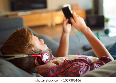 Over the shoulder image of a young caucasian guy listening to music through headphones from his phone that he is holding in his hands, all while relaxing in his lovley modern living room.