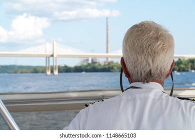 Over the shoulder POV view of a boat captain sailing down a river. Charting navigation path under bridge and past smoke stack factory on a clear summer day