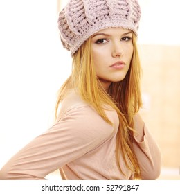 Over the shoulder profile of fashion model wearing warm pink hat and casual dress in beautiful interior at home looking at the camera