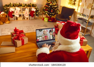 Over shoulder Santa Claus sitting at laptop computer in his workshop having video call with happy child holding Xmas present. Gift-giving, self-isolation, virtual Christmas celebration at home concept
