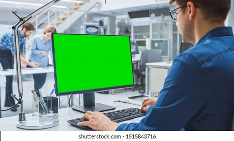 Over the Shoulder Shot of Engineer Working with Green Mock-up Screen Desktop Computer. In the Background Engineering Facility with Specialists Working on Blueprints and Drawings with Industrial Design
