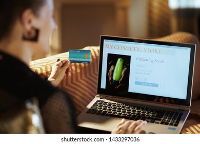 Over shoulder shot of modern woman in black blouse with credit card making beauty makeup online shopping on a laptop sitting on couch in the modern house in sunnny hot summer day.