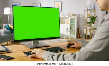 Over the Shoulder Shot of Professional Freelancer Working on Green Mockup Screen Personal Computer From Home. Man's Hands Typing, He's Browsing Through the Internet, Using Computer In the Comfort