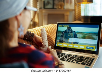 Over shoulder shot of trendy hipster in red checkered shirt with leaning tower of Pisa souvenir booking bus tickets online while laying on couch in the modern house in sunny hot summer day.