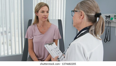 Over the shoulder shot of woman talking to her primary care doctor in exam room. Middle aged patient having appointment with female senior physician
