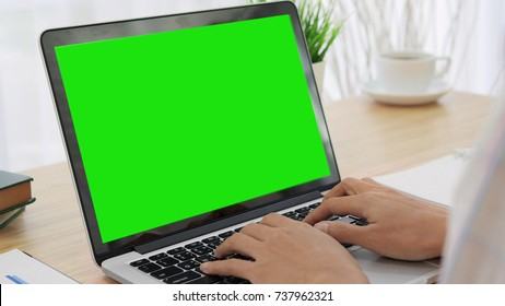 Over the shoulder shot of a woman typing on a computer laptop with a key-green screen. Woman hand typing  laptop with green screen.