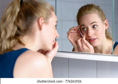 Over the shoulder view of a beautiful young woman worried about aging while looking in the mirror at the skin around her eyes