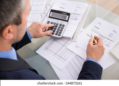 Over The Shoulder View Of Businessman Calculating Invoices Using Calculator