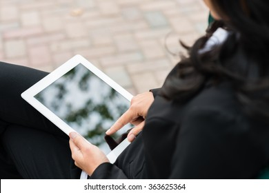 Over shoulder view of businesswoman using digital tablet computer outside