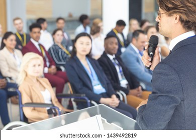 Over the shoulder view of Caucasian businessman doing a speech in conference room
