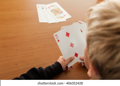 Over the shoulder view with copy space of single blond child playing cards on wooden table