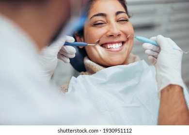 Over the shoulder view of a dentist examining a patients teeth in dental clinic. Female having her teeth examined by a dentist.
