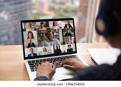 Over shoulder view of female in headset take part in distant virtual briefing video conference using laptop. Young woman employee meet with diverse colleagues online discuss work affairs on quarantine - Shutterstock ID 1906254010