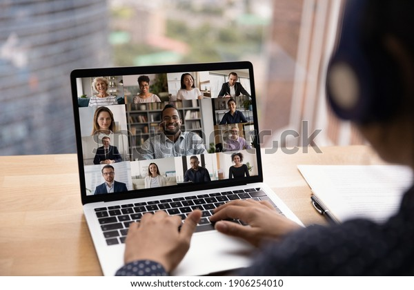 Over shoulder view of female in headset take part in distant virtual briefing video conference using laptop. Young woman employee meet with diverse colleagues online discuss work affairs on quarantine