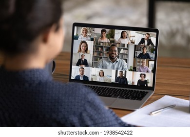 Over shoulder view of female worker have webcam digital virtual conference with diverse multiethnic colleagues. Woman speak talk on video call with multiracial businesspeople. Online meeting concept. - Shutterstock ID 1938542422