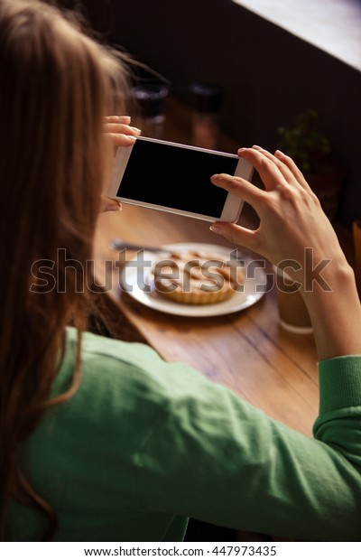 Over the shoulder view of hipster woman taking picture of pastry at cafe