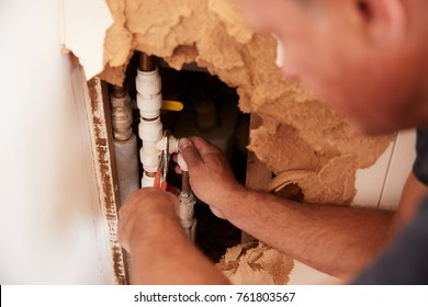 Over shoulder view of middle aged man repairing burst pipe