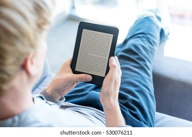Over the shoulder view of relaxing single man reading a book on digital device