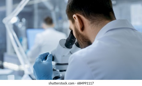 Over the Shoulder View of a Research Scientist Looking into Microscope. He's Conducts Experiments with His Colleagues in Modern Laboratory.