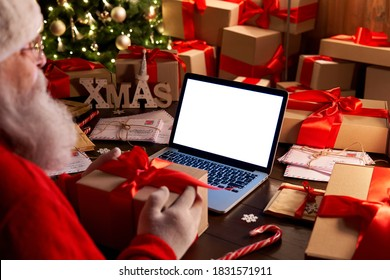 Over shoulder view of Santa Claus holding xmas gift using laptop computer with white blank empty mock up screen monitor for e commerce website ad sitting at decorated table on Merry Christmas eve.