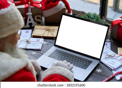 Over shoulder view of Santa Claus wearing costume using laptop computer with white blank empty mock up screen monitor sitting at workshop table on Merry Christmas eve. E commerce website ads concept
