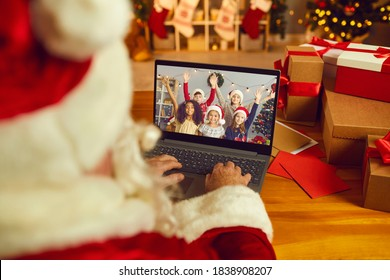 Over shoulder view of Santa Claus or Father Christmas having video call with happy diverse children on laptop computer in his workshop. Self-isolation and virtual online celebration at home concept