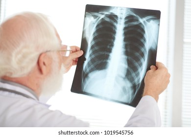 Over the shoulder view of senior doctor examining chest x-ray image
