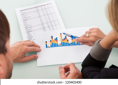 Over the shoulder view of two business partners discussing a colorful fluctuating bar graph comparing it with a text table