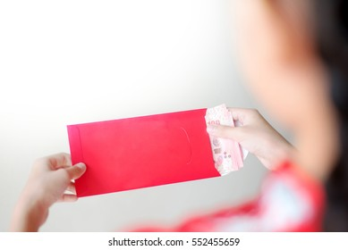 Over the shoulder view of young Asian girl with in traditional dress (Cheongsam) holding red envelope and bank note. White background and copy space.