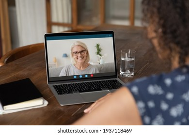Over shoulder view of young black woman taking remote course training consultation online using laptop. African female student having virtual meeting by video call with pleasant old lady tutor teacher