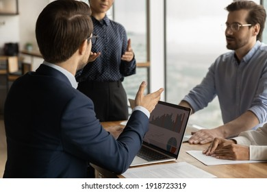 Over shoulder view of young businessman take part in corporate meeting, propose decision based on data at laptop screen. Diverse business team discuss statistical report infographics, charts share