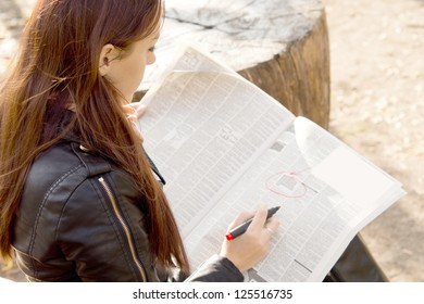 Over the shoulder view of a young female jobseeker reading the classified adverts in a newspaper and ringing them with a felt tip pen