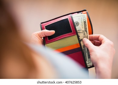 Over the shoulder view of a young woman taking US Dollar bills out of her wallet. Shallow DOF.