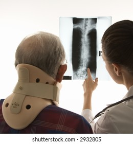 Over the shoulders view of mid-adult Caucasian female pointing at an x-ray as elderly Caucasian male in neck brace looks on.