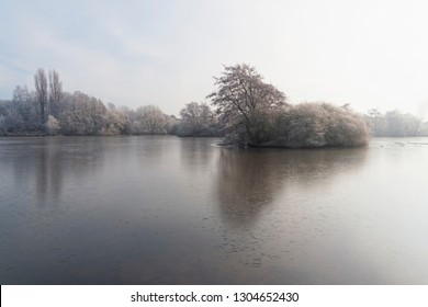 Over a small frozen lake on a cold, misty morning, to a small island of frost covered trees and bushes