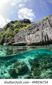 An over and under shot of the coral reef below and the limestone cliffs above the water in El Nido, Philippines.