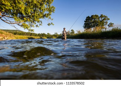 Over underwater shot of a man fly fishing in the summer in a river