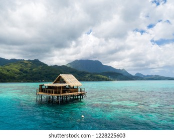 Over water bungalow of black pearl farmers. Blue azure turquoise lagoon with corals. Emerald Raiatea island, Leeward / Society islands, French Polynesia, Oceania, South Pacific Ocean near Tahiti.