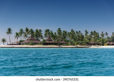 Over water bungalows on island beach with palm trees